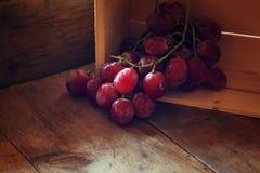Immagine scura dell'uva rossa sopra la tavola strutturata di legno Immagini Stock
