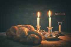 Immagine scura dello shabbat pane del challah, vino dello shabbat e candele immagine stock