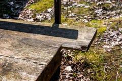 Immagine tagliata astratta di una tavola di legno solida stagionata e di un banco di legno deliberatamente vago dietro la tavola fotografie stock libere da diritti