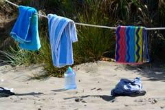 Immagine tranquilla degli asciugamani che si asciugano sulla spiaggia su una corda Immagine Stock