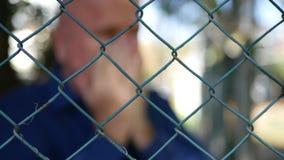 Immagine vaga con l'uomo deludente che gesticola dietro ad un recinto metallico stock footage