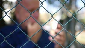 Immagine vaga con l'uomo deludente indietro di un recinto metallico Text Using Mobile video d archivio