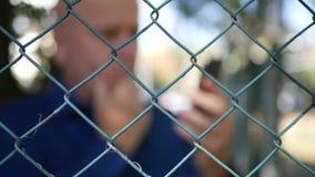 Immagine vaga con l'uomo stupito dietro il recinto metallico Read Bad News sul cellulare stock footage
