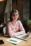 Immagine verticale della donna castana felice che si siede dalla tavola Immagini Stock Libere da Diritti