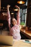 Immagine verticale della donna castana sorridente che si siede dalla tavola Immagine Stock Libera da Diritti