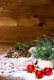 Immagine verticale della tazza con il ramo dell'abete e dei giocattoli rossi del nuovo anno su fondo di legno immagini stock libere da diritti