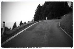 Immagini in bianco e nero della strada principale in un curbe Legame di orizzonte con la strada asfaltata Foto in bianco e nero d fotografia stock