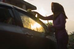 Immagini confuse del lavaggio dell'automobile della donna del hijab con la spugna gialla che lava la sua automobile davanti alla  immagini stock libere da diritti