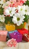 Immagini dei fiori e dei contenitori di regalo su un primo piano di legno della tavola Immagini Stock Libere da Diritti