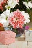Immagini dei fiori e dei contenitori di regalo su un primo piano di legno della tavola Fotografia Stock