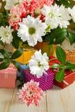 Immagini dei fiori e dei contenitori di regalo su una fine di legno della tavola su Fotografia Stock Libera da Diritti