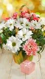 Immagini dei fiori e del contenitore di regalo su un primo piano di legno della tavola Fotografia Stock