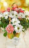 Immagini dei fiori e del contenitore di regalo su una fine di legno della tavola su Fotografie Stock
