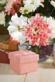 Immagini dei fiori e del contenitore di regalo su una fine di legno della tavola su Fotografia Stock