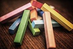 Bastoni variopinti del gesso su superficie di legno Immagini Stock