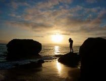Immagini della fucilazione dell'uomo mentre stando su una roccia del litorale di Laguna fotografia stock