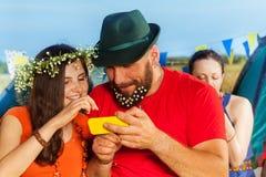 Immagini di sorveglianza delle giovani coppie felici allo smartphone Immagine Stock Libera da Diritti