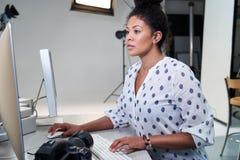 Immagini femminili di In Studio Reviewing del fotografo dal tiro di foto sul computer fotografia stock libera da diritti