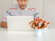 Immagini vaghe degli uomini anziani asiatici che godono dell'uso dei computer portatili sulla tavola bianca, sta studiando l'uso  immagine stock libera da diritti
