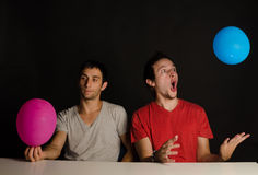 Immature guys. Two immature guys fooling around with balloons stock images