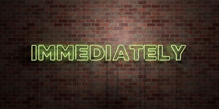 IMMEDIATELY - fluorescent Neon tube Sign on brickwork - Front view - 3D rendered royalty free stock picture Royalty Free Stock Photo