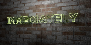 IMMEDIATELY - Glowing Neon Sign on stonework wall - 3D rendered royalty free stock illustration Royalty Free Stock Photos