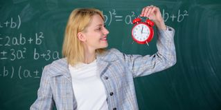 Immer rechtzeitig Lehreringriffwecker Sie interessiert sich für Disziplin Zeit zu studieren Willkommenes LehrerSchuljahr lizenzfreie stockfotografie