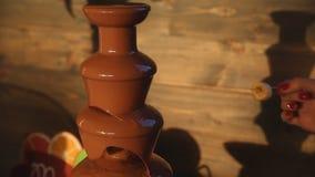 Immergendo una banana in una fontana del cioccolato archivi video