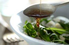Immergendosi in olio sopra all'insalata verde Immagini Stock