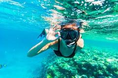 Immergersi subacqueo della donna con il nuoto giusto del segno nel mare fotografie stock