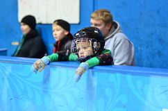 Immersed in dreams. The little boy in the hockey helmet standing at the side looking at what is happening in the hockey arena and immersed in dreams Stock Photography