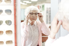 Immersed mature female person in optic store Royalty Free Stock Image