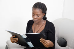 Immersed in reading. This young woman is highly concentrated in the reading of her documents this morning Royalty Free Stock Photography