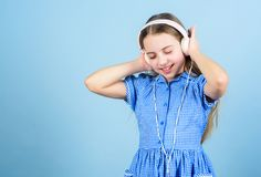 Immersing in music. Adorable child enjoy music playing in earphones on blue background. Little girl enjoying her royalty free stock photos