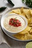 Immersion de fromage cr?meuse faite maison dans une cuvette, puces de tortilla jaunes au-dessus de la surface en bois blanche, vu photo stock