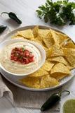 Immersion de fromage faite maison dans une cuvette, puces de tortilla jaunes au-dessus du fond en bois blanc, vue de c?t? Plan ra images stock