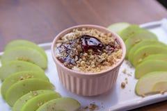 Immersione di Apple di caramello con i dadi, il condimento del caramello e le fette fresche della mela fotografia stock