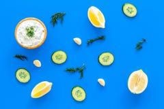 Immersione greca del yogurt con pianta, cetriolo, arance, aglio sul modello blu di vista superiore del fondo Fotografia Stock