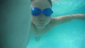 Immersione subacquea castana del ragazzo & Selfie di presa sotto l'acqua nella piscina Un colpo subacqueo stock footage