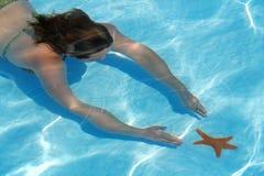 Immersione subacquea della donna per le stelle marine Fotografia Stock Libera da Diritti