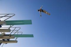 Immersione subacquea della giovane donna dal trampolino immagini stock libere da diritti