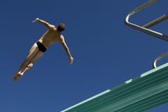 Immersione subacquea maschio del nuotatore dal trampolino Immagini Stock