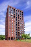 Immeuble caractéristique de brique rouge contre un ciel bleu avec les nuages dramatiques, Tilburg netherlands Photographie stock libre de droits