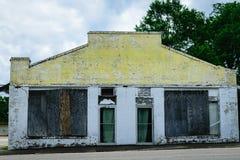 Immeuble de brique jaune et blanc abandonné Photos stock