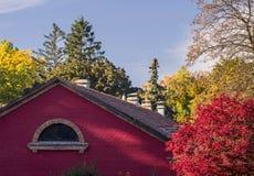 Immeuble de brique rouge parmi les arbres d'automne avec des feuilles de rouge et de jaune image libre de droits