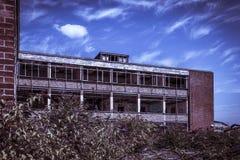 Immeuble de bureaux abandonné de brique rouge sous un ciel bleu Images libres de droits