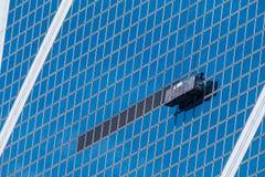 Immeuble de bureaux avec la plate-forme de fonctionnement suspendue Photos libres de droits