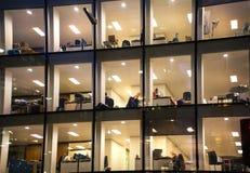 Immeuble de bureaux avec un bon nombr'à l'intérieur allumées de fenêtres et de défunts employés de bureau Ville d'aria d'affaires Photo libre de droits