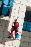 Immeuble de bureaux de nettoyage d'homme accrochant sur des cordes Images stock