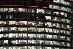 Immeuble de bureaux moderne avec des hublots la nuit Images stock